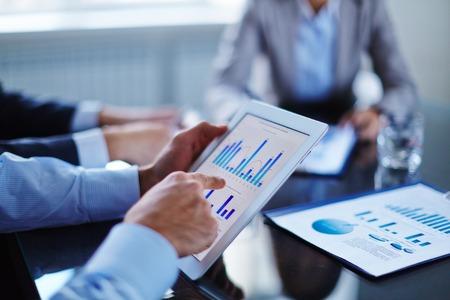 사업: 차트와 터치 스크린을 가리키는 사업가