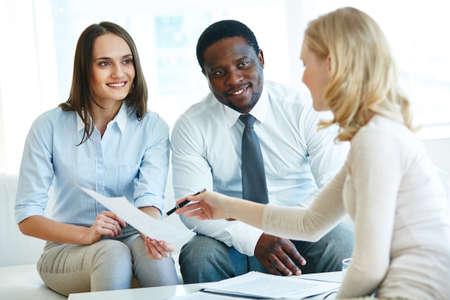 explaining: Businesswoman explaining point in document to colleague