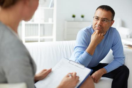 Hombre pensativo en anteojos escuchar psicólogo