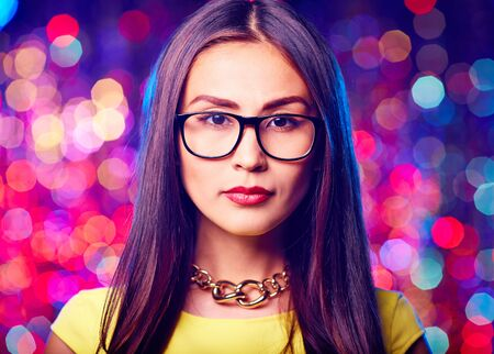 adult entertainment: Young Asian woman in eyeglasses looking at camera on sparkling background