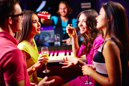 drinks on bar: Young friends talking at party while drinking champagne