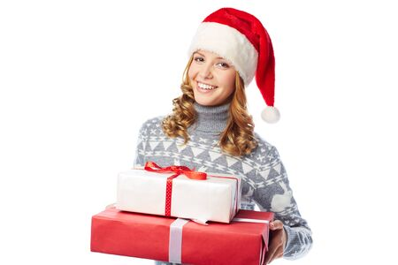 christmastide: Young woman in Santa cap holding packages with Christmas gifts