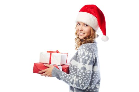 christmastide: Pretty girl in sweater and Santa cap holding Christmas surprises Stock Photo