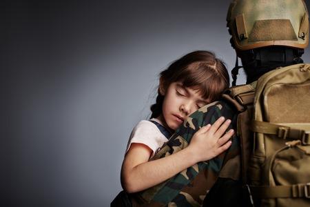 Kind van de slaap gehouden door krijger in camouflage