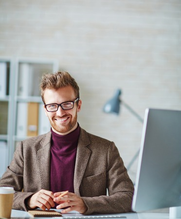 smiling businessman: Young businessman sitting in office and looking at camera with toothy smile Stock Photo