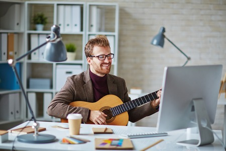 contemporary: Young businessman with guitar looking at computer while singing in office