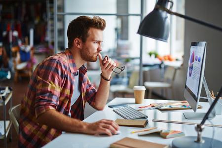 Design moderne assis en face de l'ordinateur dans le bureau Banque d'images - 47436811