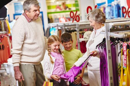 Grandmother showing new tanktop for granddaughter in the mall photo