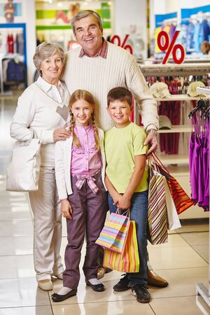 Happy grandparents and their grandchildren standing in one of departments of mall photo