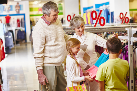 Grandparents choosing new clothes for granddaughter and grandson photo