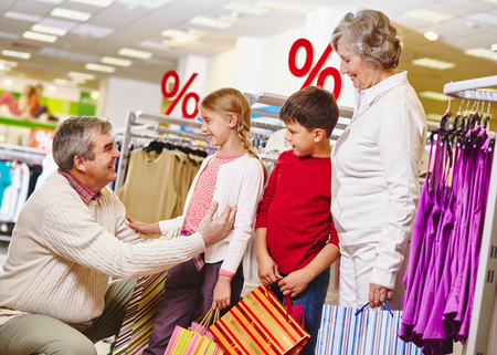 elderly adults: Grandparents and their grandchildren shopping together