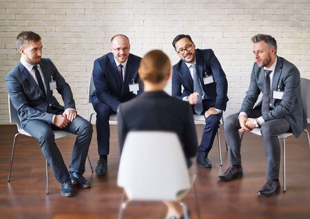 delegate: Modern businessmen listening to colleague answering to their questions Stock Photo