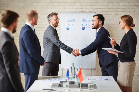 handshaking: Foreign business partners greeting one another by handshaking Stock Photo