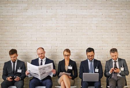 Gut gekleidete Geschäftsleute warten auf die Reihe zu interviewen Standard-Bild