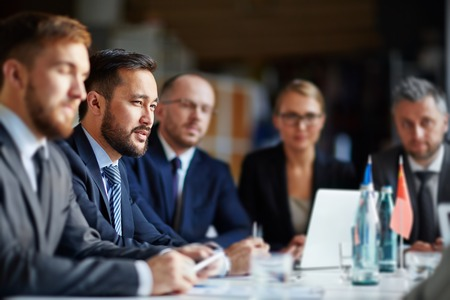 Successful businesspeople listening to lecture at conference or seminar photo