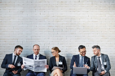 Modern business people communicating while sitting against brick wall photo