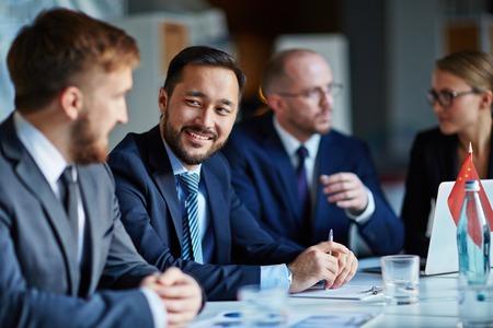 Aziatische zakenman op zoek naar zijn partner tijdens de bespreking van de punten van de conferentie
