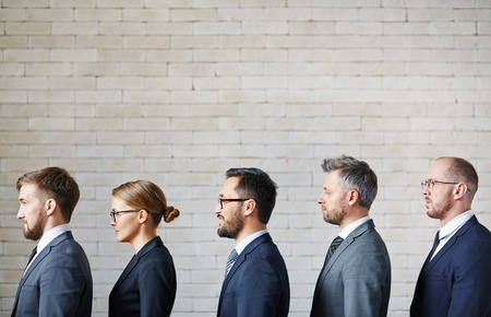 employee: Several employees standing in queue along wall Stock Photo