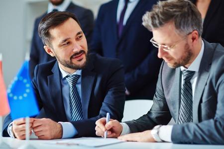 Asian businessman looking at his partner during negotiation photo