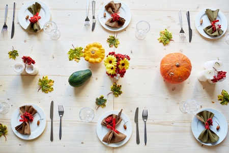 festive occasions: Ripe ashberries, flowers, candles and squashes on table