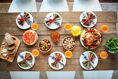 thanksgiving: Roasted poultry, glasses with juice, vegetables, nuts and tableware on served table Stock Photo