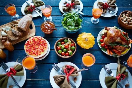 turkey: Pavo asado, vasos con jugo, verduras, nueces, postre, pan fresco y vajilla en la mesa de la cena Foto de archivo
