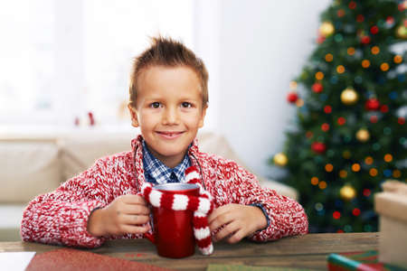 holiday tradition: Cute youngster with red cup looking at camera