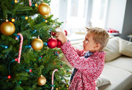youthful: Youthful child decorating Christmas tree with decorative toy bubbles