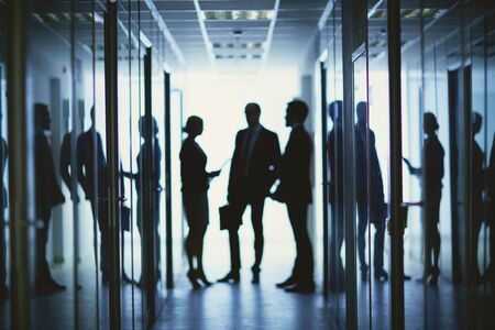 office meeting: Blurred silhouettes of business people having meeting in corridor of office center