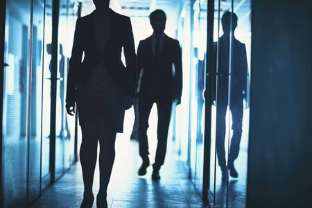 go inside: Office workers walking down corridor of business center