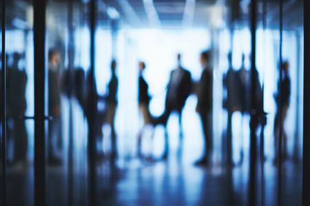 silueta hombre: Siluetas borrosas de la gente de negocios que interactúan en el pasillo del centro de la oficina Foto de archivo