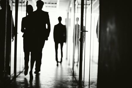 go inside: Outlines of business people walking along corridor of office center Stock Photo