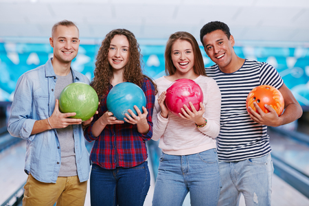 competitive sport: Cheerful friends with bowling balls looking at camera