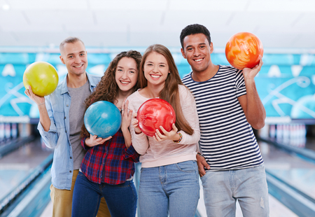 jovenes felices: Group of joyful young friends with bowling balls looking at camera