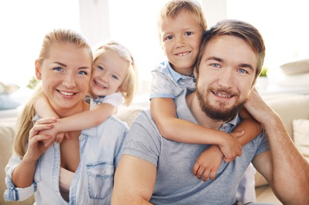 boy beautiful: Happy and affectionate kids embracing their mother and father Stock Photo