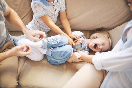tickling: Happy girl laughing while her mother and brother tickling her