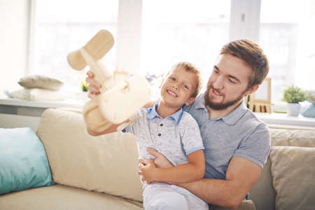 adult toys: Adorable boy with wooden airplane playing with his father