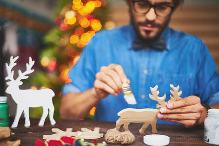 christmas symbol: Young man painting toy Christmas symbol