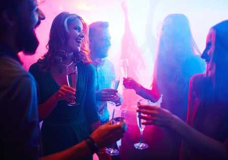 party friends: Cheerful friends with champagne spending time in night club Stock Photo