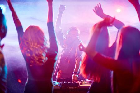 Energetic people dancing in front of ecstatic dj