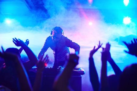 Energieke deejay staande voor dansende mensen in club