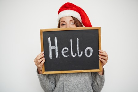 christmastide: Young girl in Santa cap looking at camera out of blackboard