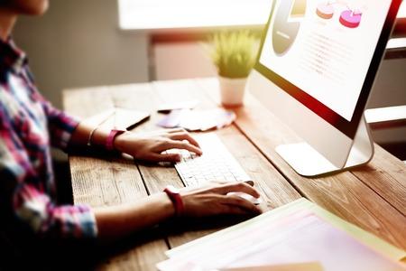 informático: La mujer joven se sienta delante de la pantalla del ordenador