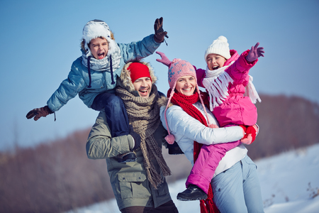 ecstatic: Ecstatic family in winterwear looking at camera outdoors