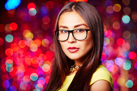 clubber: Pretty young woman in eyeglasses looking at camera at party