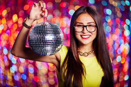 clubber: Pretty girl with disco ball and toothy smile looking at camera