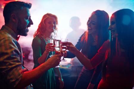 clubber: Cheering friends with champagne enjoying party in nightclub