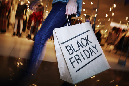 black: Modern shopper with Black Friday paperbag going in the mall
