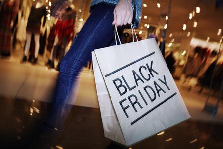 Shopper moderno con el Viernes Negro paperbag va en el centro comercial