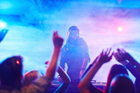 dancing club: Energetic deejay and dancing crowd enjoying disco in night club Stock Photo
